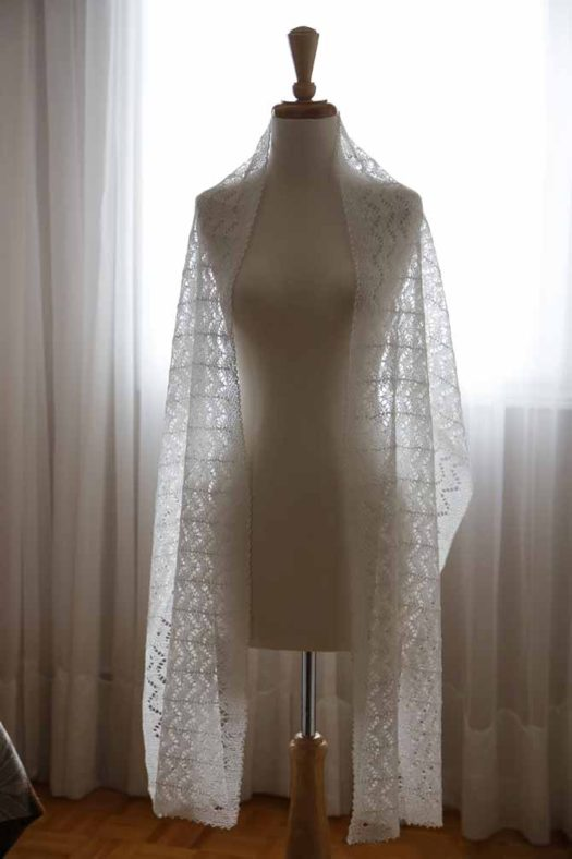 The Wedding Stole knit up with Universal Yarns Flax Lace in white, on a mannequin