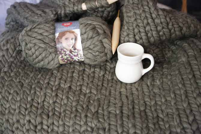 My daughter's blanket is very soft and textured at the same time. I placed a cup of 11oz to show you how big the ball of yarn is, and how big the knit is too. Red Heart Boutique Irresistible yarn in Taupe
