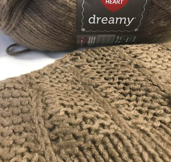 A close up of the stitches used in this shawl. The lace stitch carries one knit stitch up while the rest is in garter. There are occasion eyelettes throughout.