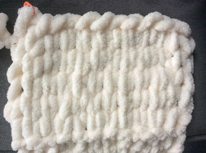 """The scale of the stitches makes the """"V"""" of each stockinette stitch in this sample clearly visible. The orange stitch marker is just there to hold my last cast off stitch in place."""