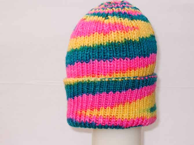This acrylic toque has a wedge of hot pink where the decreases begin, and the colors start to spiral in the opposite direction to the rest of the hat.