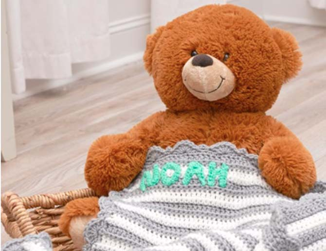 A teddy bear with a white and grey striped blanket. The baby's name is stitched on with a teal yarn.