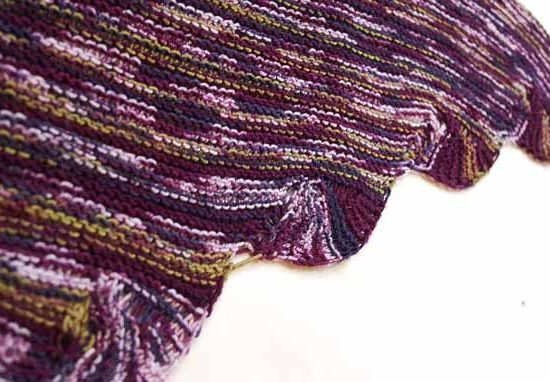 Edge of triangular scarf featuring scalloped edges, all worked in garter stitch