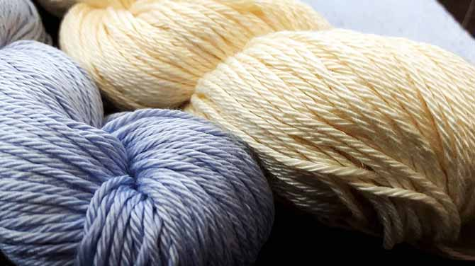 Two hanks of Radiant Cotton yarn in a soft periwinkle blue and a warm custardy cream color