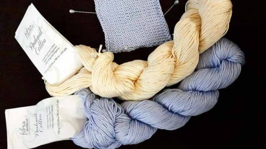 A light periwinkle blue hank and a creamy light custard hank of Radiant cotton beside a stockinette swatch