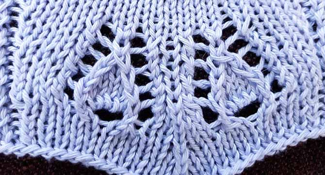 close up of two leaf motifs in knitted lace leaning towards a central double decrease