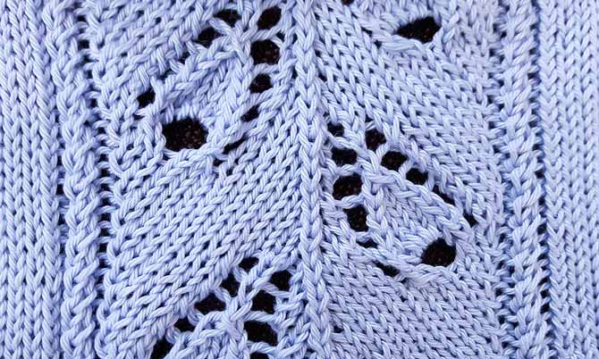 Close-up of knitted stole with lace motifs that are staggered instead of parallel to each other.