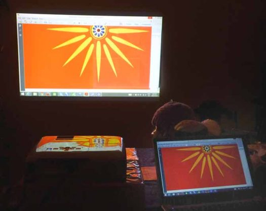 The lower half of the vergina sun projected onto the wall, with the graph paper taped on the right side. In the foreground, the image is reflecting off the top of the projector on the left, and the image is on the laptop screen on the right.