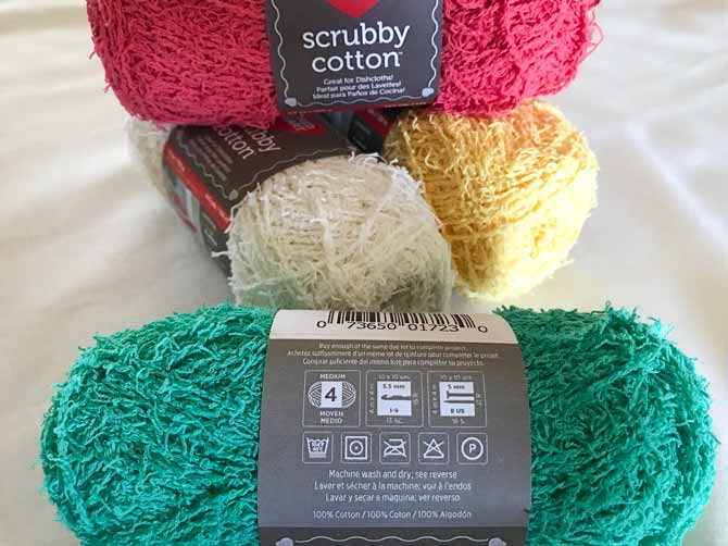 A ball of Scrubby Cotton yarn in the color Jade in front of the other three colors. This shows the label with washing instructions machine wash and dry.