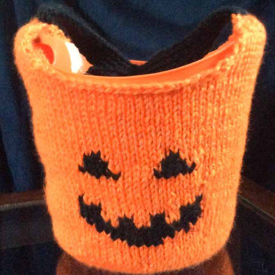 An orange jack-o-lantern bag with a plastic lining sitting on a table with a dark backdrop.