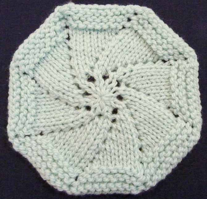 A mint colored circle knitted from the center out, made with yarn over increases at the beginning of each of the 8 repeats which makes right-leaning spirals appear.