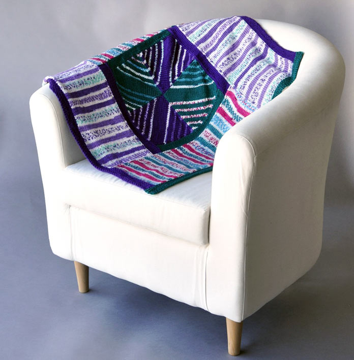 This stunning blanket makes the most of these self-striping yarns and highlights them by framing them in intensely saturated solid colors.
