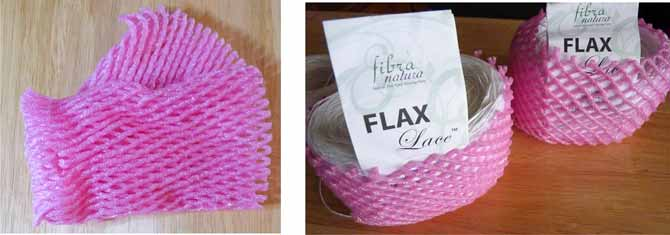 Pink foam protectors from the produce department get wrapped around two cakes of Flax Lace yarn. The labels have been temporarily tucked into the packages which sits on a wooden table.